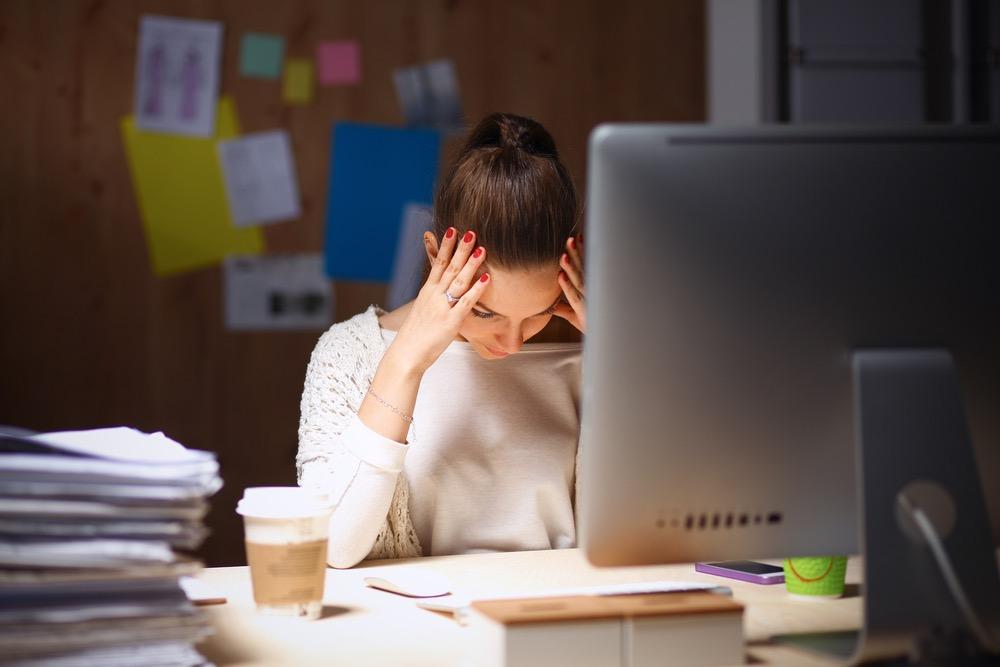 暗いオフィスで頭を抱えて悩む女性
