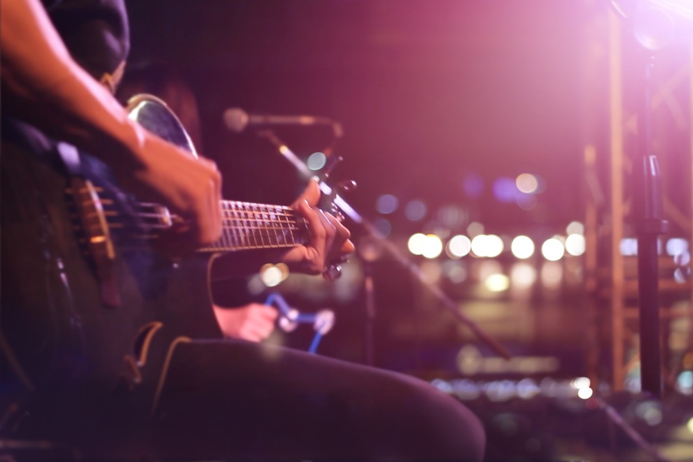 ステージでギターを弾くバンドマン