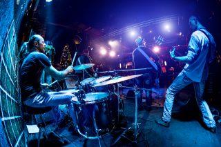 ステージでドラムを叩くバンドマン