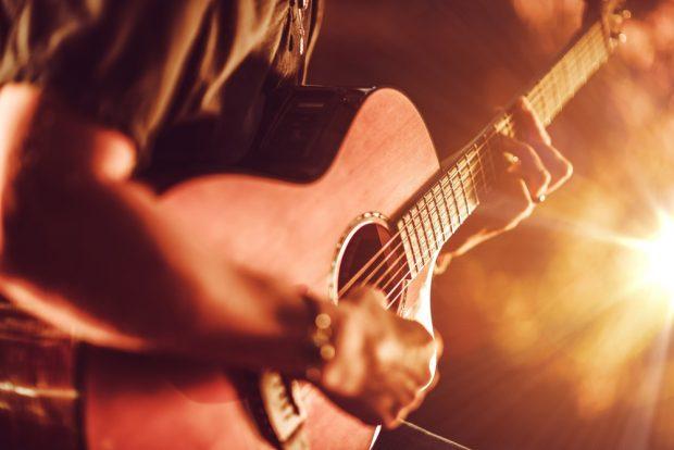 ライトを浴びながらギターを弾く男性