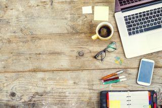 ノートパソコンや筆記用具が散らばった机の上