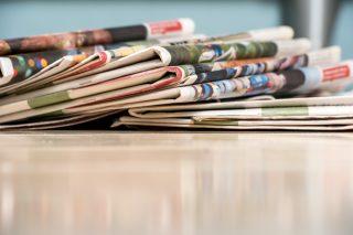 机の上に重ねて置かれた新聞紙