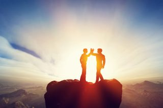 岩の上でハイタッチする男性二人のシルエット
