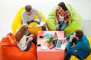 カラフルなビーズクッションに座って談笑する男女のグループ