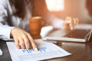 グラフの書かれた書類を見ながら仕事をする女性