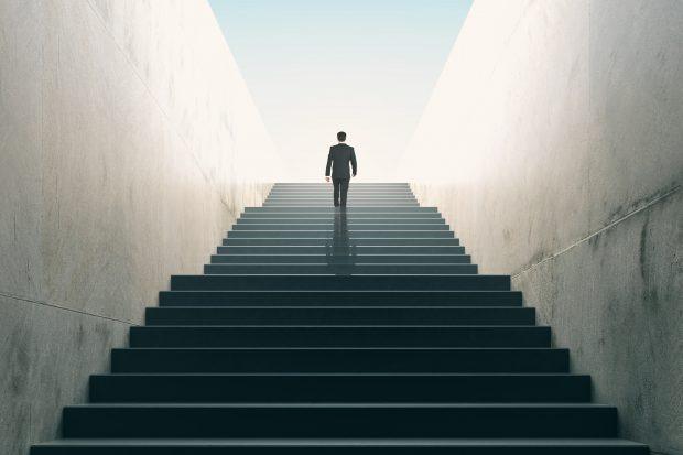 階段を登るスーツを着た男性