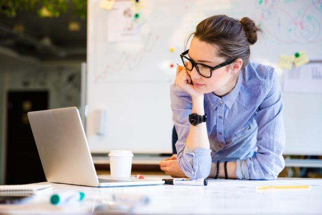 厳しい表情でノートパソコンを見つめる女性