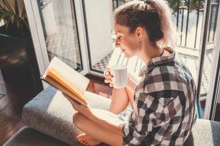明るい窓際で勉強する女性