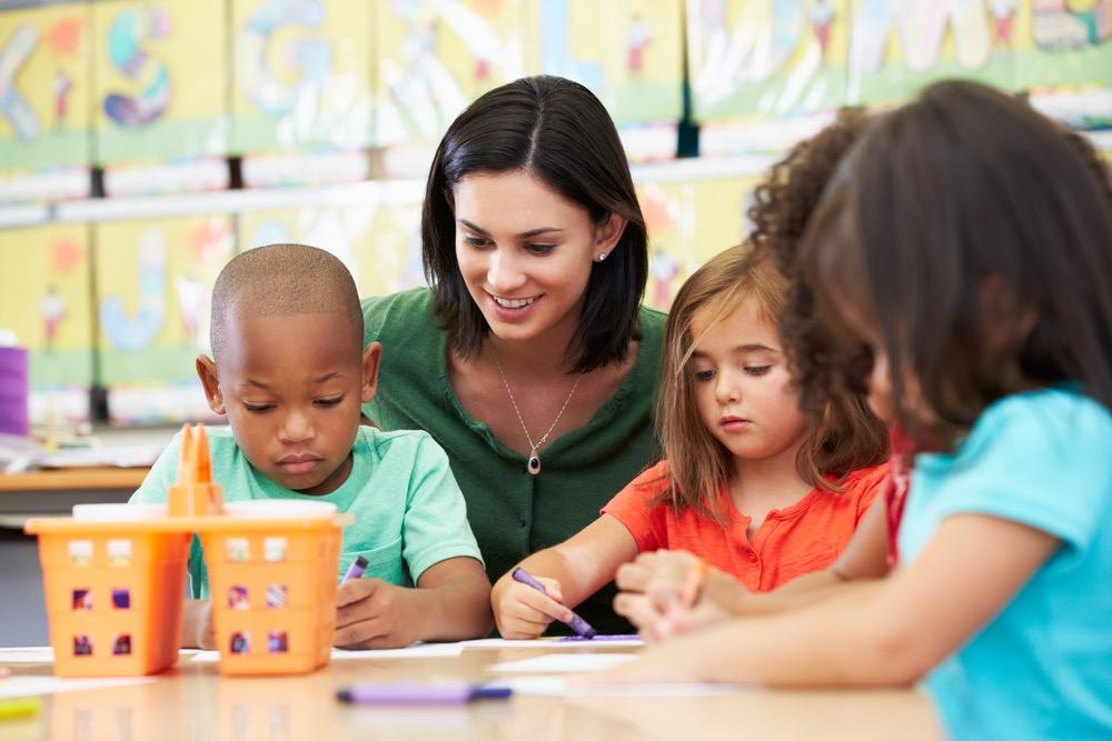 子供達とお絵描きをする女性