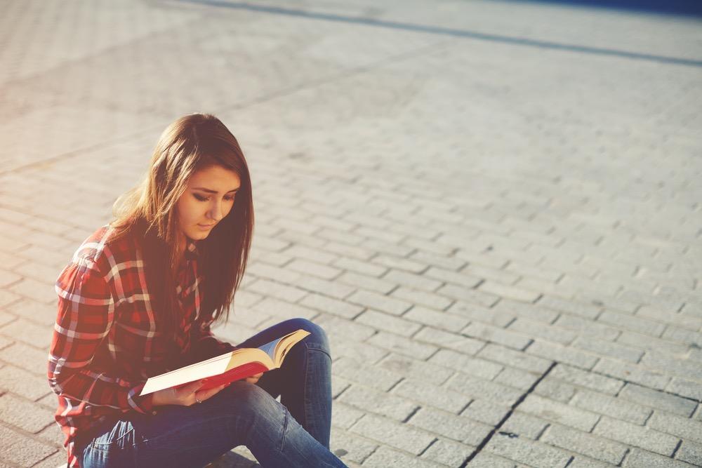 道に座り込んで本を読む女性