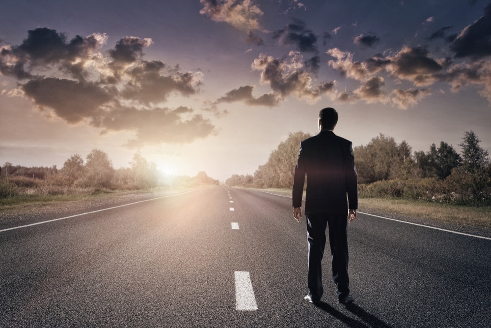 長い一本道に立つ男性