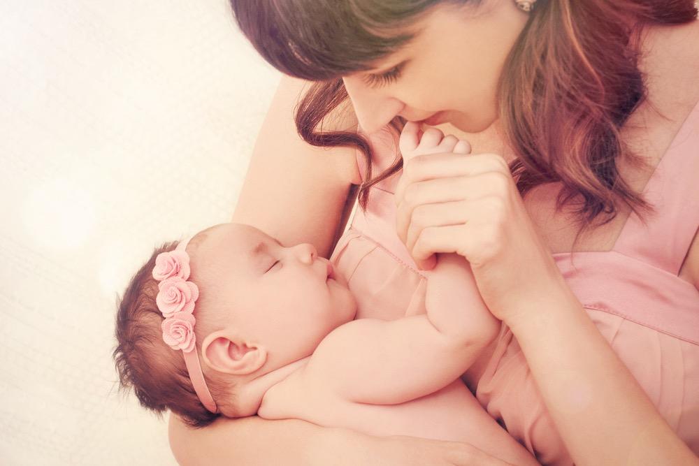 赤ちゃんを抱いて指にキスする女性