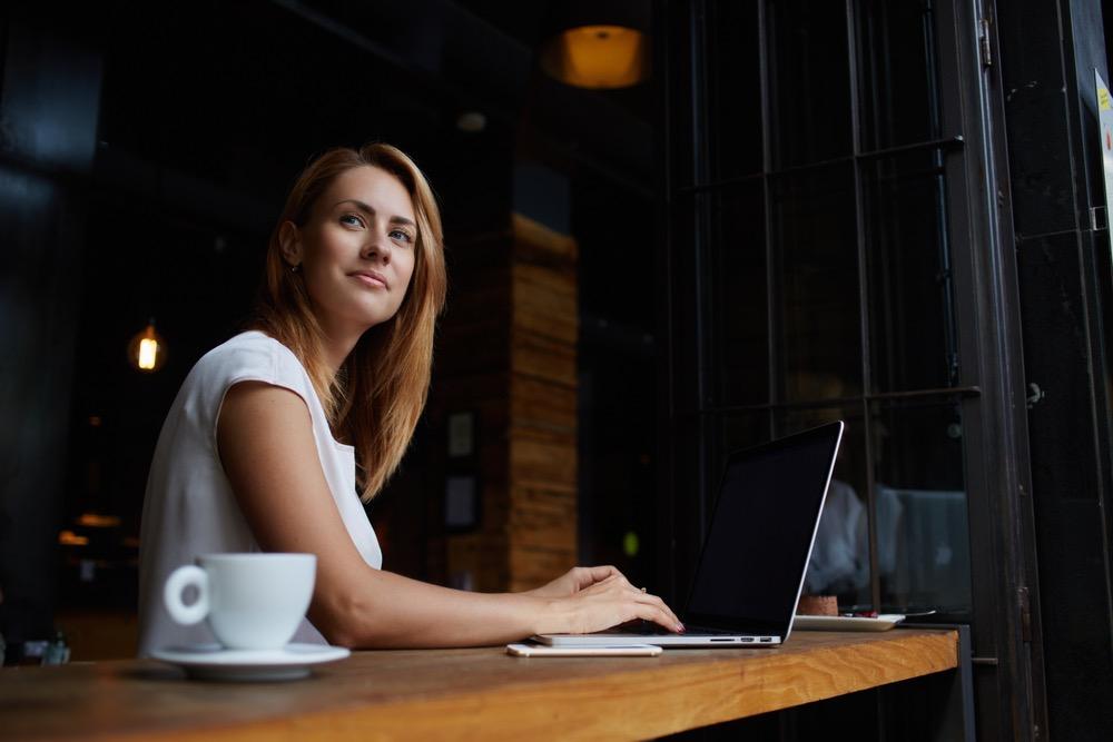 カフェでノートパソコンを開いて仕事をする女性