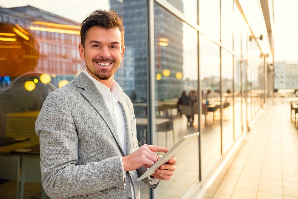 タブレットを操作している笑顔の男性