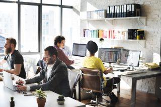 明るいオフィスでデスクワークする人々