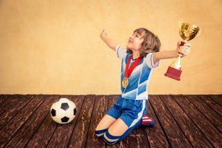 サッカーで優勝して笑顔の少年