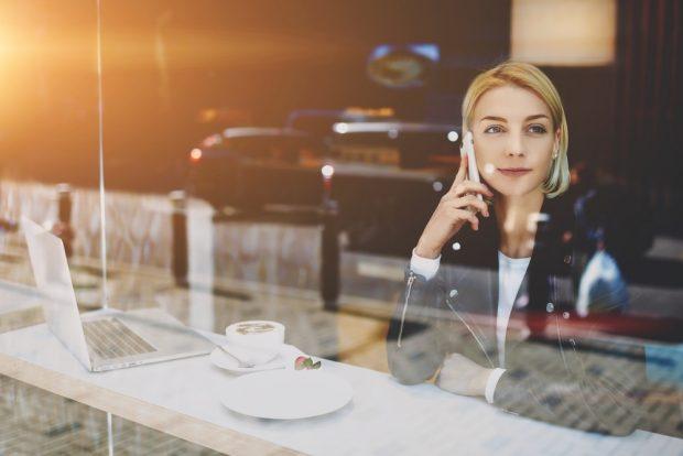 カフェで仕事をしながら電話をする女性