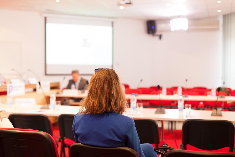 会見場に座る記者の女性