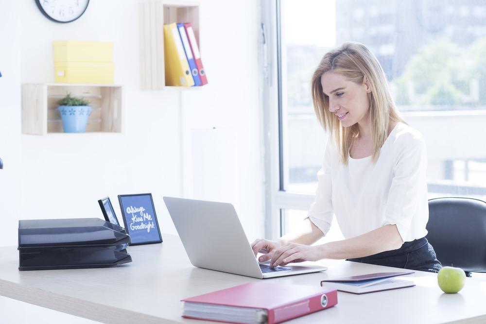 ノートパソコンを開いて仕事をする金髪の女性