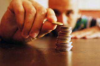 机の上にコインを積み重ねる人