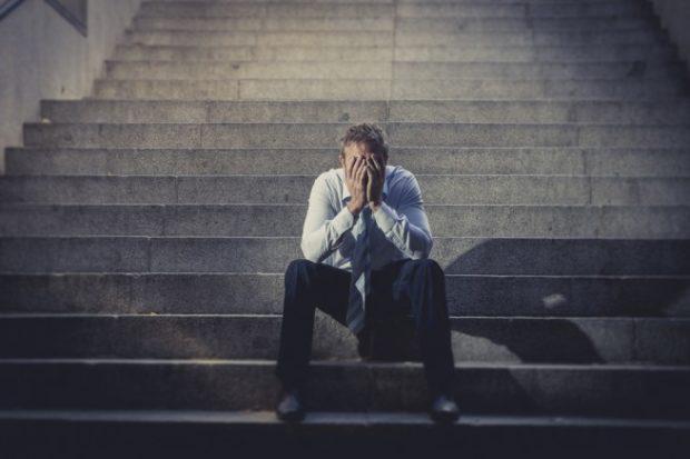 階段に座り、絶望するように両手で顔をおおうスーツの男性