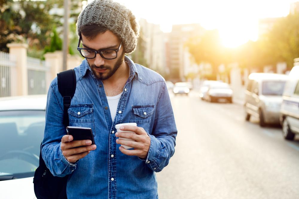 テイクアウトのコーヒーを手にしながらスマートフォンを見る男性