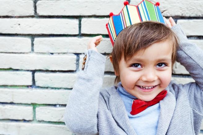 おもちゃの王冠をかぶって笑う、蝶ネクタイをした少年