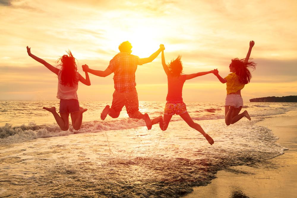 波打ち際で手を繋いでジャンプする人達のシルエット