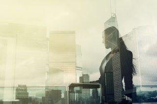 スーツを着た女性とビジネス街の風景