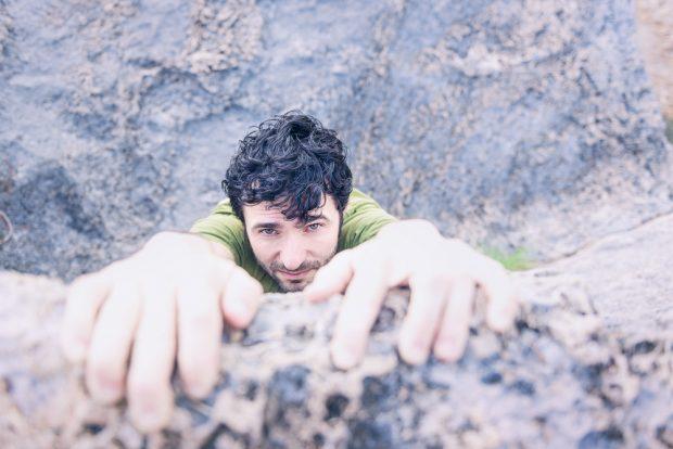 崖っぷちにつかまり苦しそうな顔でぶら下がる男性
