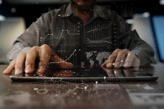 上昇するグラフとタブレット端末を操作する人