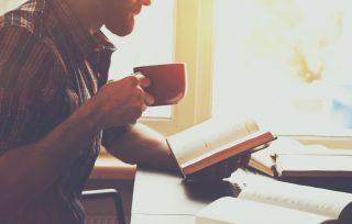 本を読みながらマグカップを口に運ぶ男性