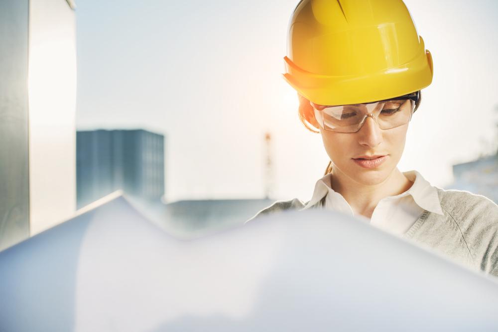 安全帽をかぶって建設現場で設計図を見る女性