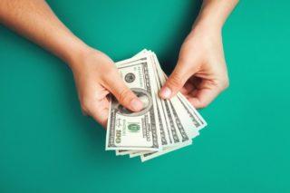 100ドル札を広げる手