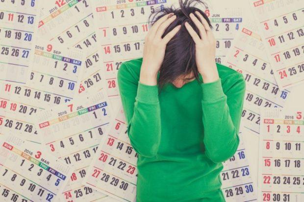 めくり終わったカレンダーの中で頭を抱える女性