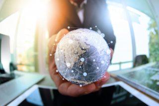 地球儀を持つ男性とネットワークのイメージ