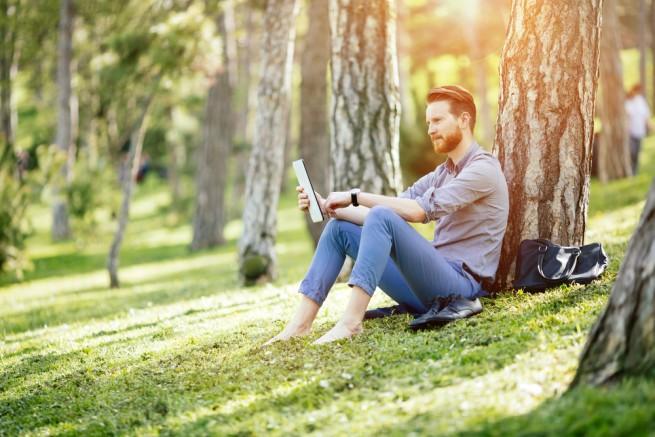 自然の中で靴を脱ぎ木にもたれてくつろぎながら、タブレット端末を見る男性