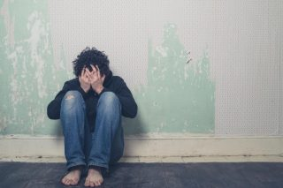 ボロボロの壁の前に座り込み絶望する男性