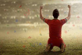 サッカー場の芝生に膝をつきガッツポーズする男性