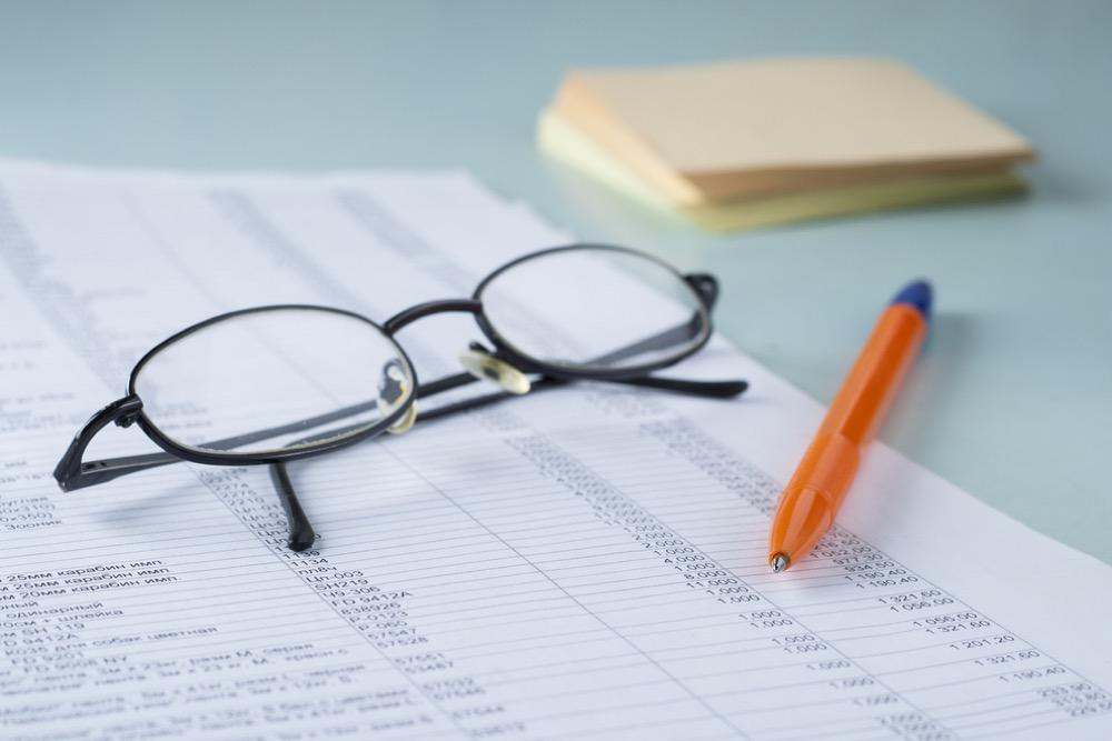 メガネとボールペンと会計書類