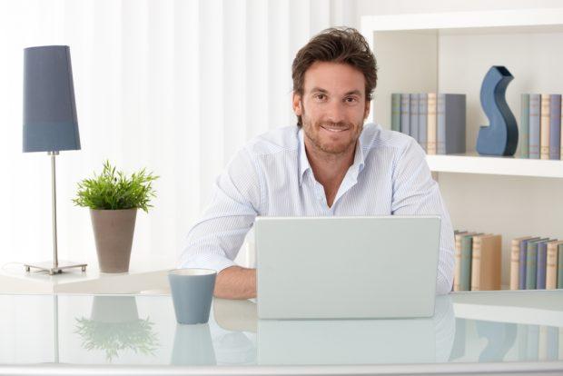 明るいオフィスで仕事中の笑顔の男性