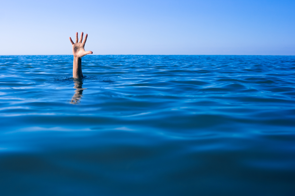 海で溺れて助けを求める男性の手