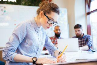 設計図を書く黒縁メガネをかけた女性