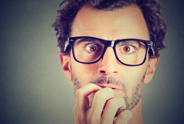 驚いた顔で爪を噛むメガネをかけた男性