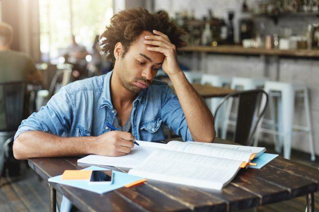 額に手を置き難しそうな表情で勉強する男性