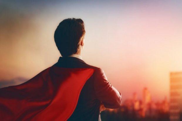 オフィス街で夕焼けを見つめるスーパーヒーロー