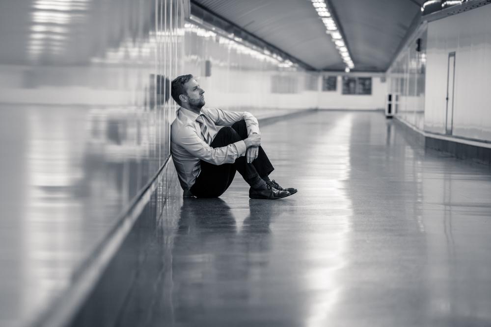 長い廊下で落ち込んだ男性が壁にもたれかかっている