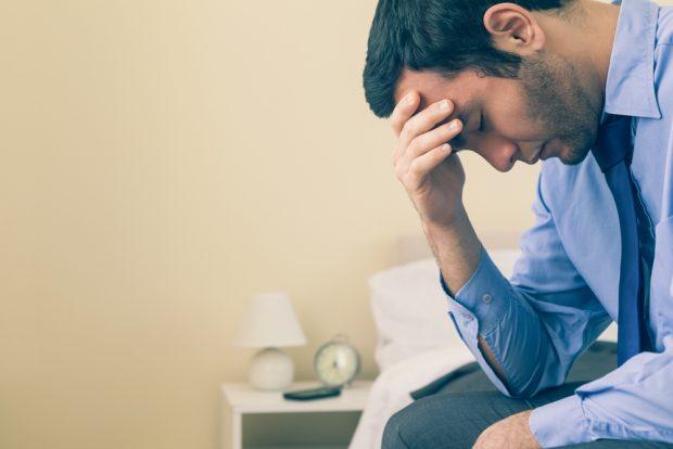 頭を抱えて悩む男性