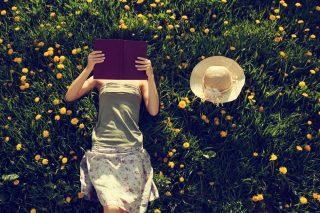 草原に寝そべり本を読む女性
