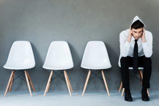 複数ならぶ椅子の一つに座り、呆然とする男性